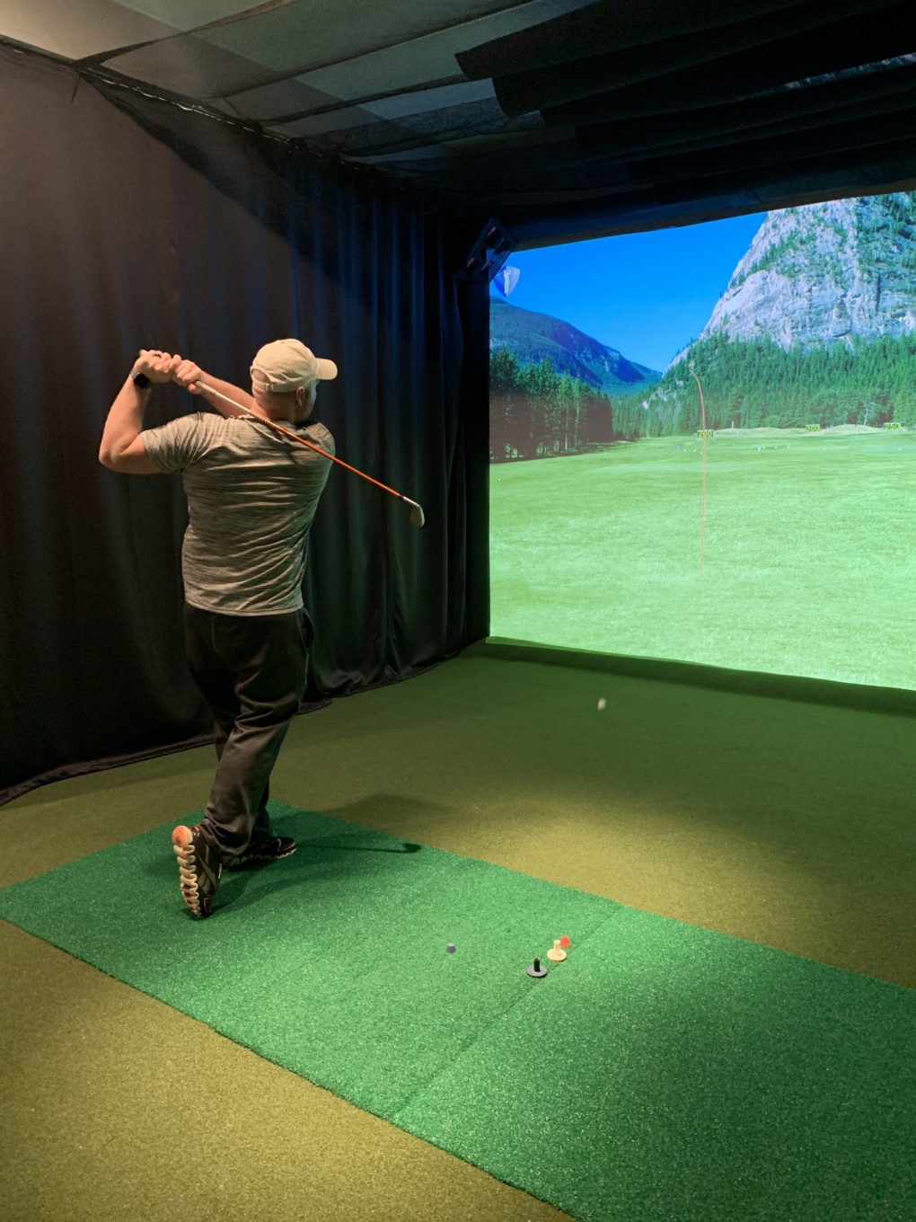 man using indoor golf simulator